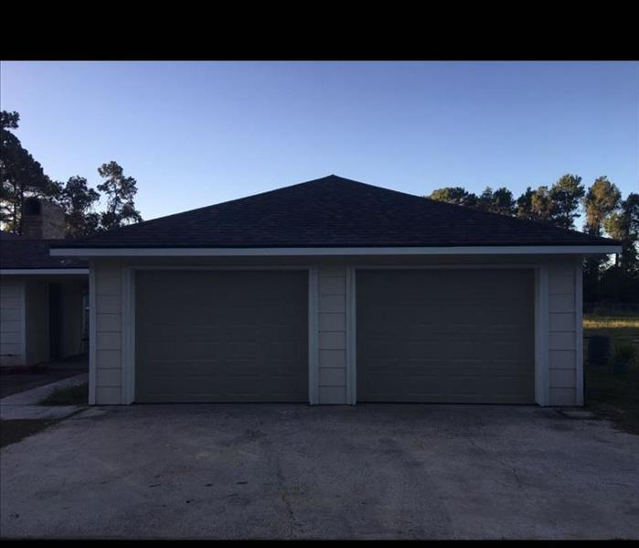 Same garage, completely rebuilt. Painted tan with darker tan garage doors, doors closed, concrete slab in front of garage