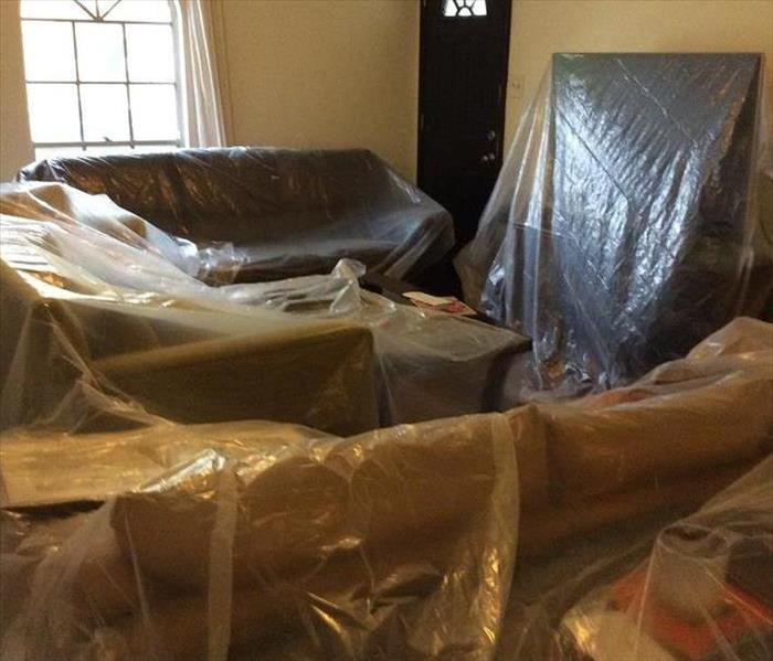 Furniture covered in protective plastic in a home.