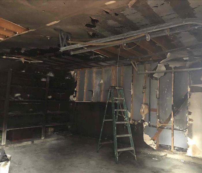severe fire damage to garage. big chunks of sheetrock missing, ladder in middle of garage. ceiling missing some parts