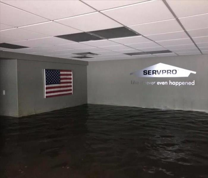 building with water almost up to the ceiling, SERVPRO house on right wall, American flag on left wall