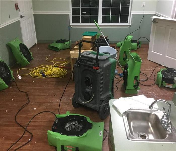 room with green SERVPRO equipment all over, sink in bottom right corner, window on back wall