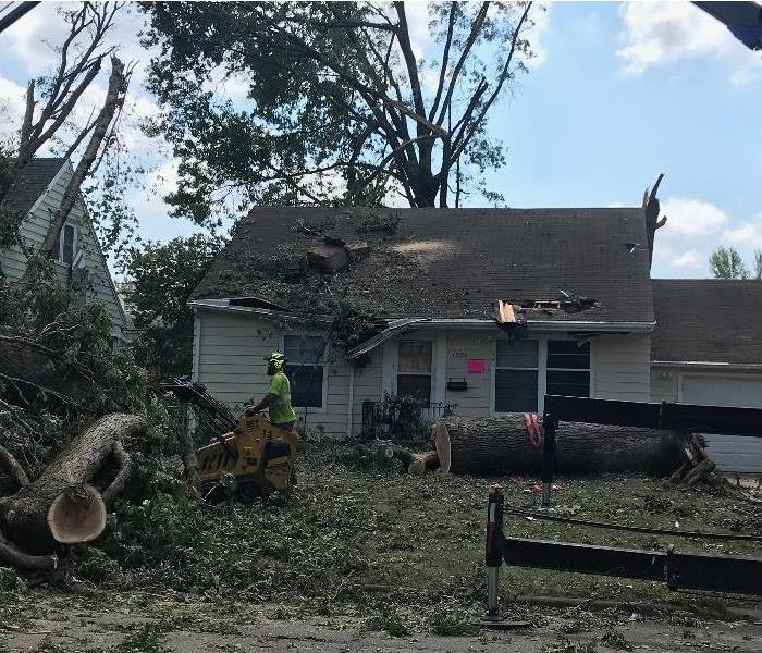 House with trees fallen down in yard, roof damaged with tree debris on top