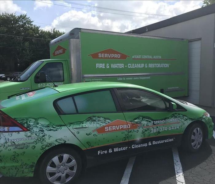 green car with SERVPRO information on side, green box truck behind car with SERVPRO information on side of truck