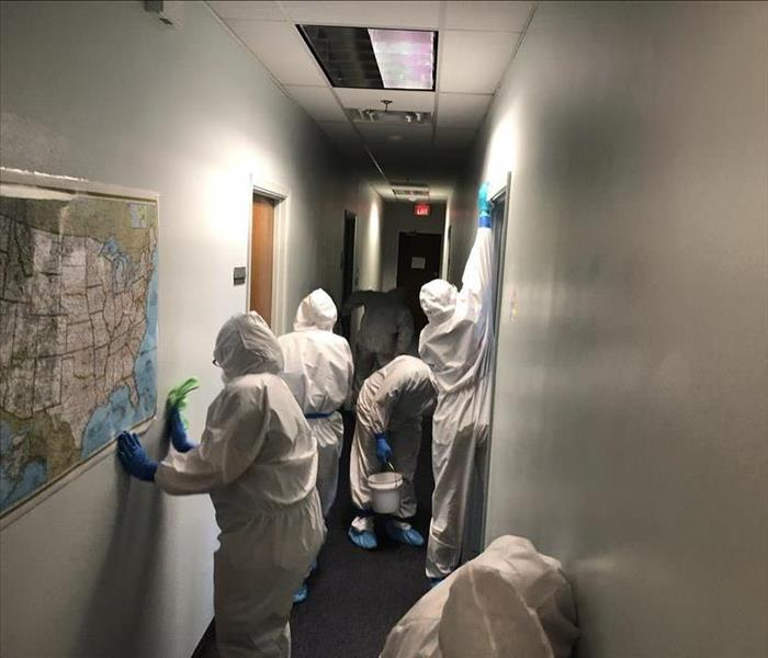 hallway in building, 6 people in full white protective body suits, wiping down walls.