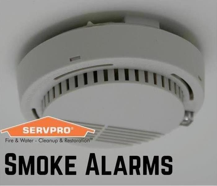 "smoke detector on ceiling with orange servpro house in bottom left corner and ""smoke alarm"" under the servpro house."